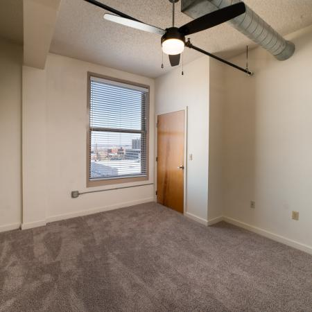 Carpeted bedroom with ceiling fan and closet