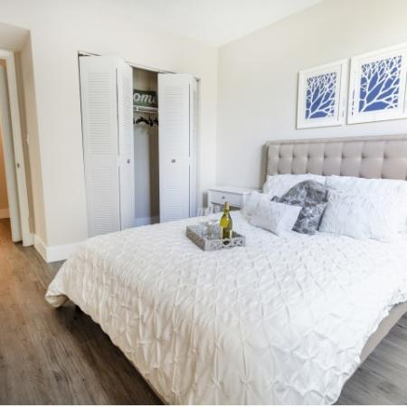 Furnished master bedroom with bed, nightstand, and dresser with closet and en suite bathroom