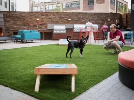 Resident Playing Corn Hole | Apartment Homes In Quincy | West of Chesnut