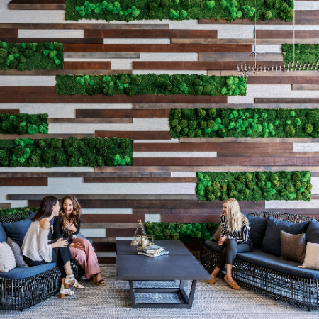 people enjoying seating by living wall