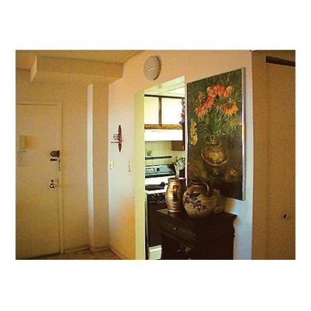 Queenswood Apartments, interior, apartment front entrance, view into kitchen, stove/oven, white and would framed cabinet