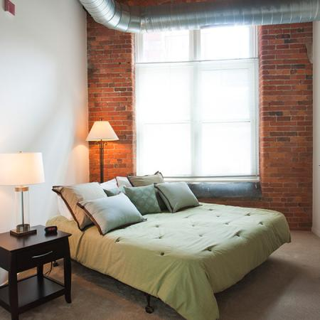bedroom in modern richmond loft with green bed and brick
