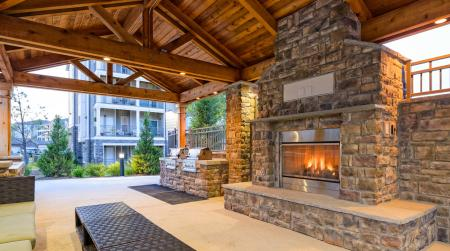 Outdoor fireplace lounge with BBQ grills at Atley on the Greenway in Ashburn, VA