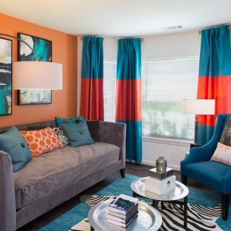 Bright living room with colorful drapes at Grand Reserve Orange Apartments in Orange, CT.