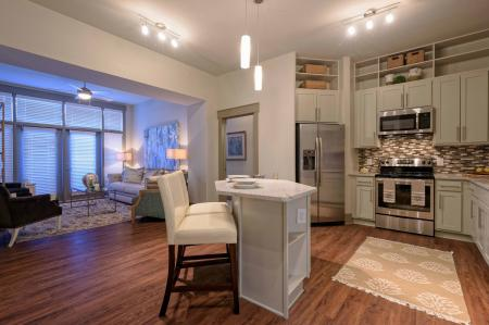 Living room and kitchen open floorplan in 1160 Hammond Apartments in Sandy Springs, GA