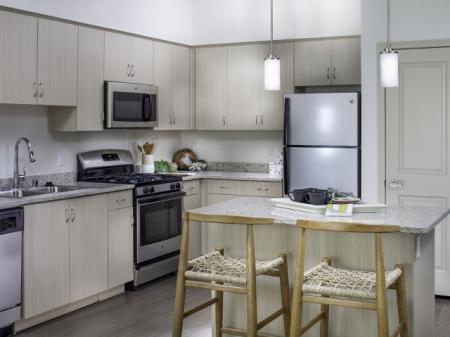 Modern kitchen with light color scheme at Pulse Millenia in Chula Vista, CA