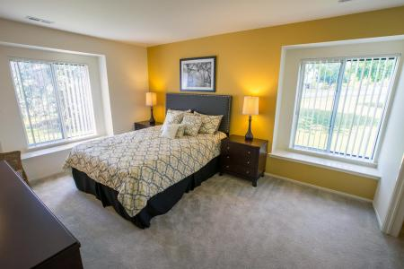 Bedroom with built-in window seats at Oaks at Hampton Apartments in Rochester Hills, Michigan