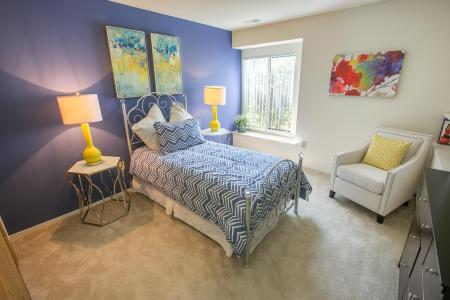 Bedroom with built-in bookshelves at Oaks at Hampton Apartments in Rochester Hills, Michigan
