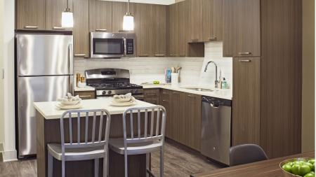Sleek color scheme: modern quartz countertops and dark espresso cabinetry at Mave Apartments in Stoneham, MA