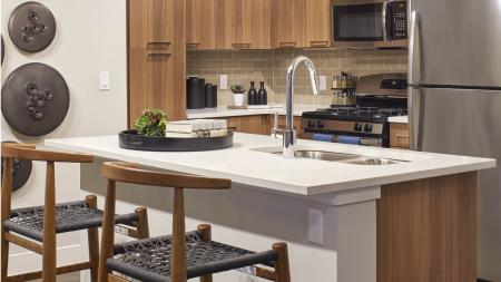 Harmony color scheme: beautiful quartz countertops and natural cabinetry at Mave Apartments in Stoneham, MA
