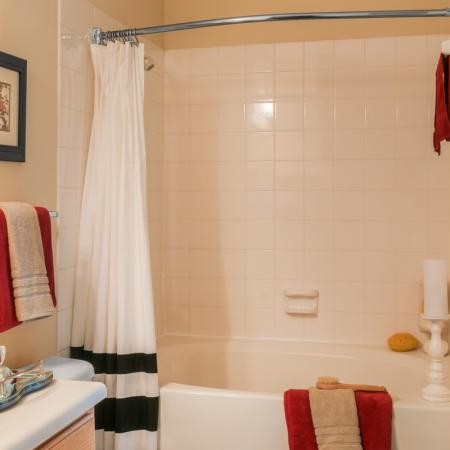 Bathroom with tile surround tub and shower at River Pointe at Den Rock Park Apartments in Lawrence, MA