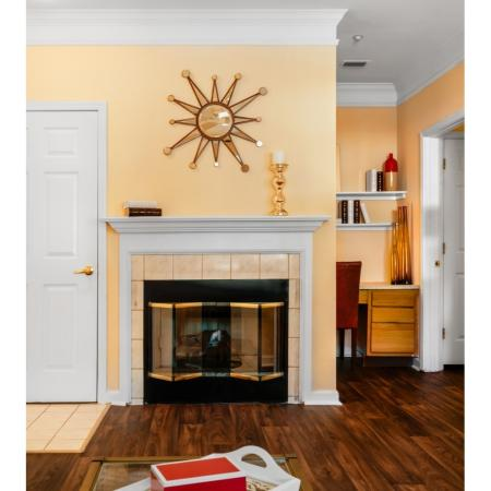 Elegant fireplace, crown molding, and wood-style floors at River Pointe at Den Rock Park Apartments