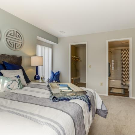 Bedroom with attached bath and walk-in closet at Oaks at Hampton Apartments in Rochester Hills, MI