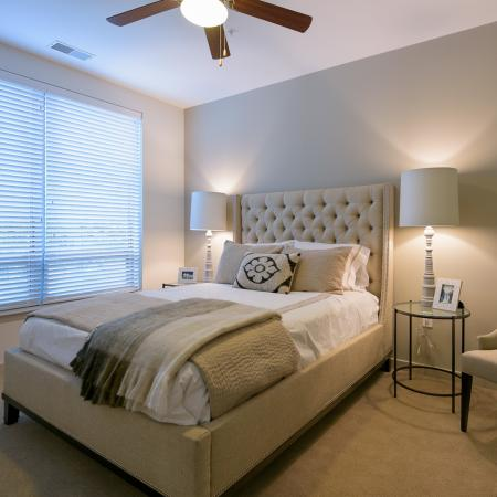 Spacious bedrooms with ceiling fan and large windows for natural light