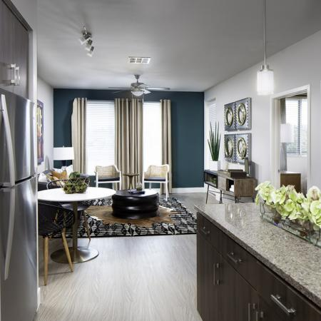 Kitchen and living room at Vela on OX Apartments in Woodland Hills CA