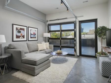 Living room with track lighting, garage door window, and custom stained concrete floors.