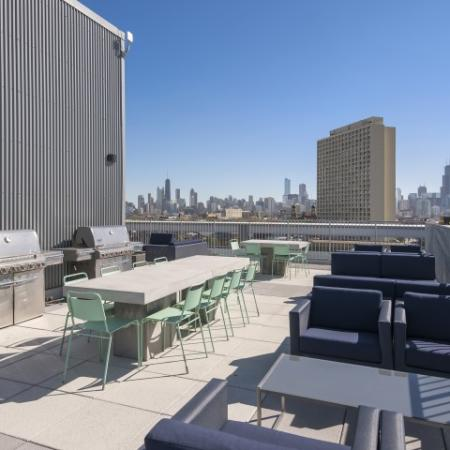 Rooftop deck with grills and comfortable seating.