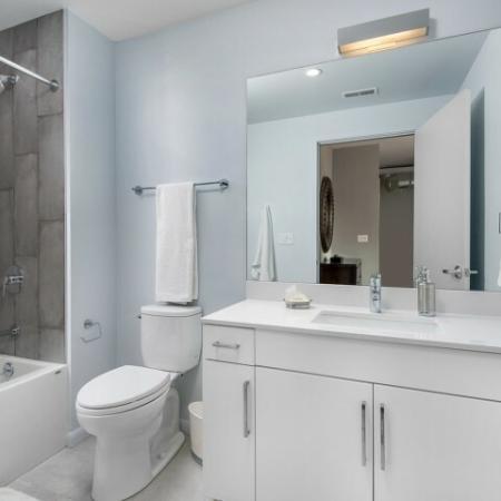 Bathroom with shower, bathtub, and tile flooring.