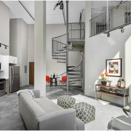 Living room with custom stained concrete floors, kitchen with stainless steel appliances, and staircase leading to loft.
