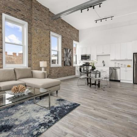 High ceilings and exposed brick with plank flooring