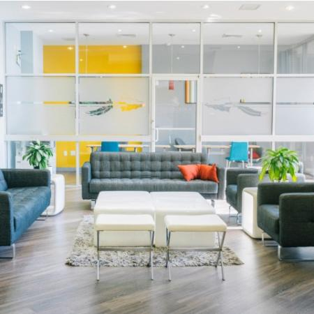 The Renegade, interior, seating area, natural light, yellow wall, glass wall, windows, gray sofas, wood floor,