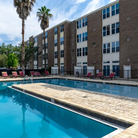 The Osceola, exterior, sparkling blue swimming pool, palm trees, lounge chairs, building