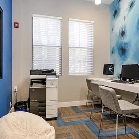 Computer room with two Macs, one PC, a heavy duty printer, and art