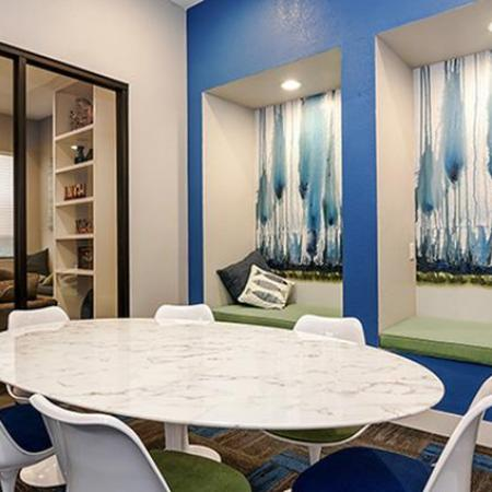 Enclosed group study room with table and six chairs as well as two wall nooks with soft seating.