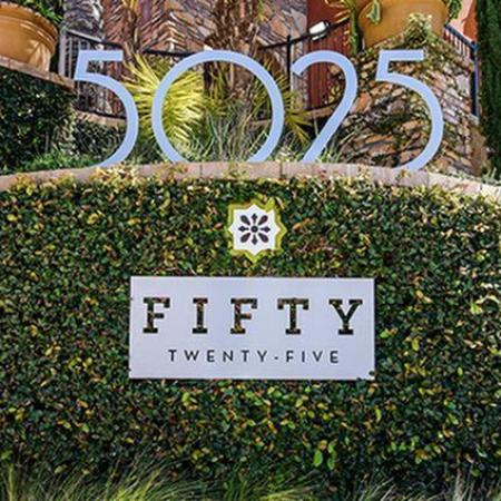 Building signage with Fifty Twenty-Five logo and bushes