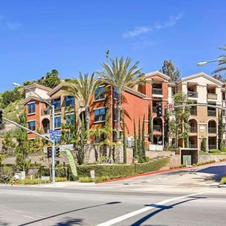 Exterior of apartment building lined with palm trees with two crosswalks directing to the community