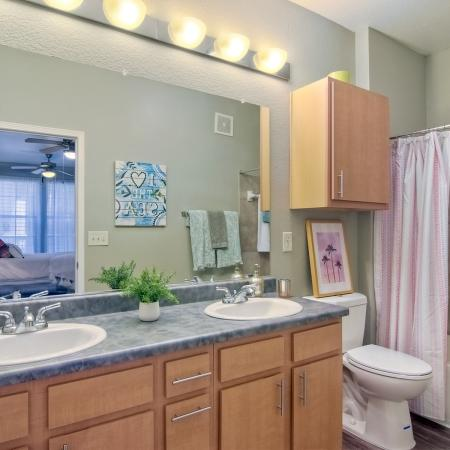 Model apartment bathroom with double sinks, toilet, and shower