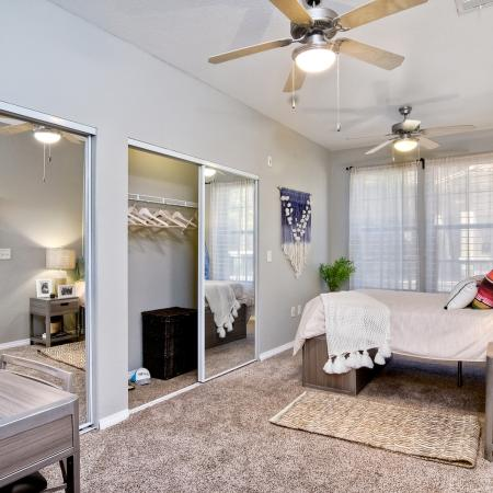 Model apartment bedroom with two large mirrored closets