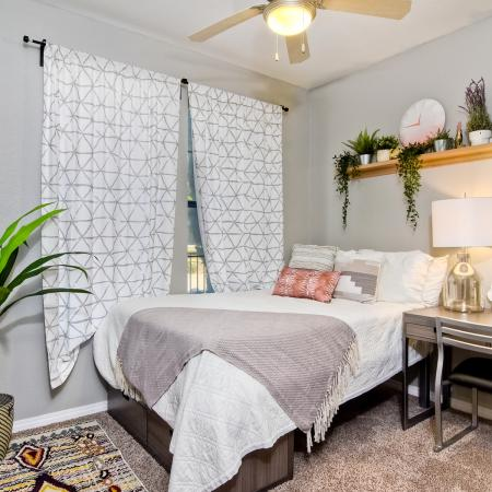 Model apartment bedroom with a bed, desk, chair, and decorations