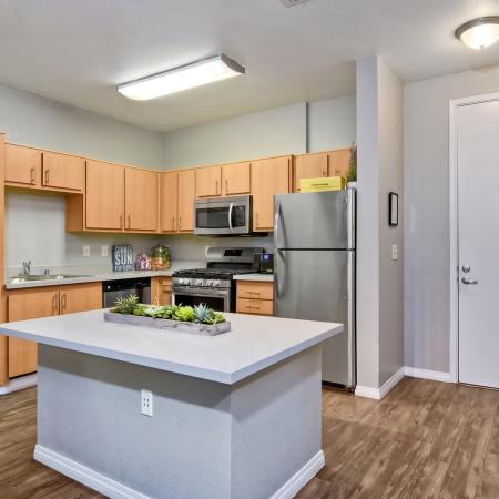 Model apartment kitchen with center island, stainless steel appliances, and modern cabinetry