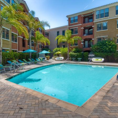 Courtyard pool with brick paving, pool chairs, and palm trees