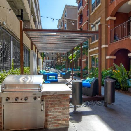 Gas BBQ grill overlooking courtyard with outdoor seating arrangements