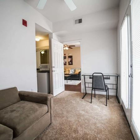 The Osceola, interior, living room, carpet, desk, chair, sofa, door to outside, ceiling fan, doorway to mini kitchen,