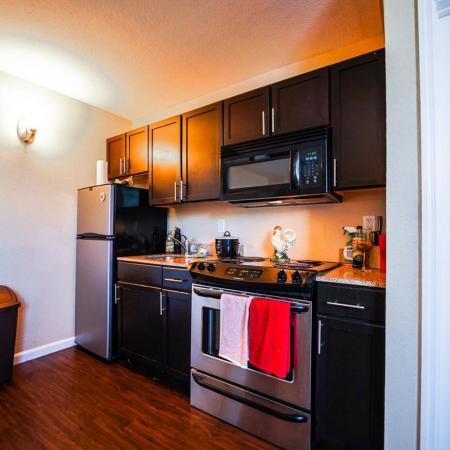 The Osceola, interior, kitchen, wood floor, dark cabinets, stainless steel appliances