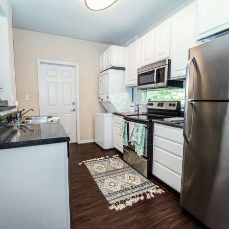 The Osceola, interior, kitchen, wood floor, white cabinet, stainless steel appliances, white stacked washer/dryer