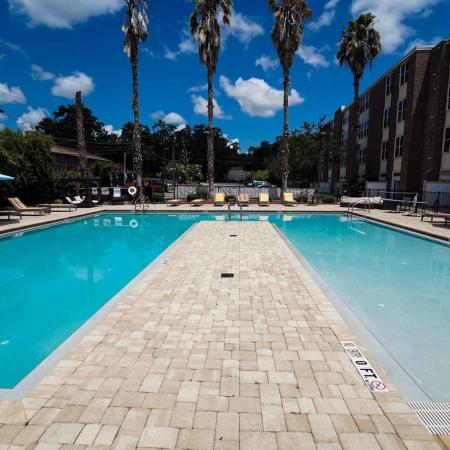 The Osceola, exterior,  sparkling blue swimming pool, palm trees, lounge chairs, building on the right