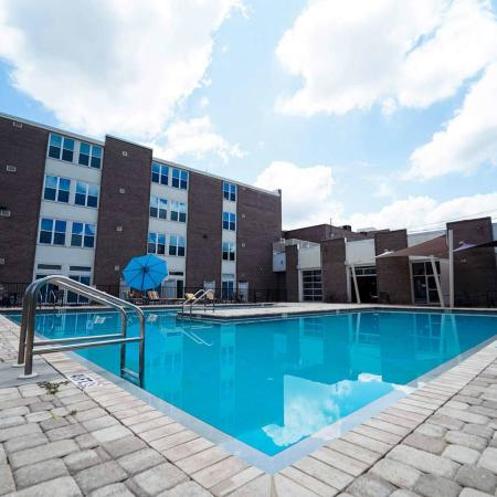 The Renegade, exterior, sparkling blue swimming pool, palm trees, lounge chairs, building