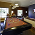 Residents playing pool and watching TV in the game room at The Reserve on West 31st