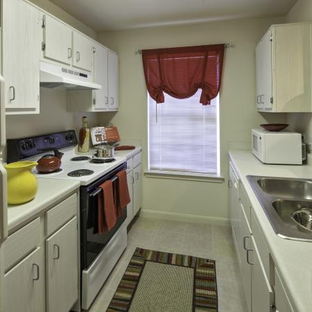 Refrigerator, counters, cabinets, stove, microwave, and sink in a kitchen at Cayce Cove
