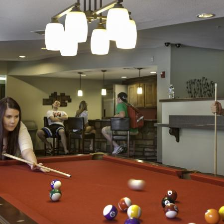 Game room with pool table and bar seating
