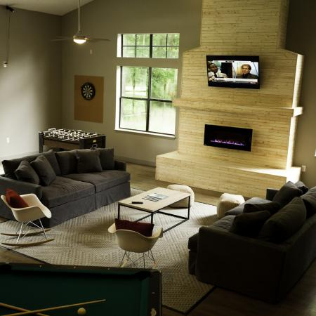 Game room with foosball, sofas, a TV, and a fireplace at The Pavilion on 62nd