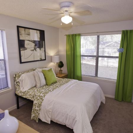 Furnished bedroom with a bed, dresser, and ceiling fan at The Pavilion on 62nd
