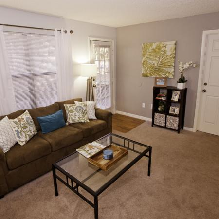 Living area with sofa, tables, carpet, and a patio door at The Pavilion on 62nd