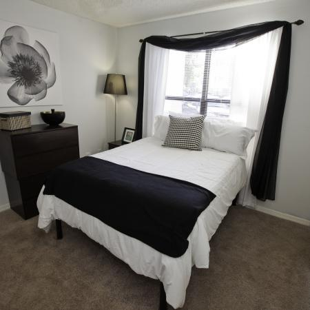 Furnished bedroom with bed and dresser at The Pavilion on 62nd Apartments