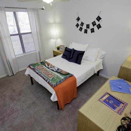 Furnished bedroom with a bed, dresser, and desk at Pavilion on 62nd Apartments