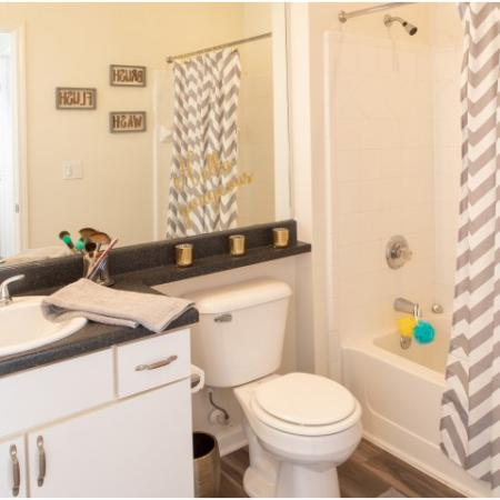 Spacious bathroom with updated white cabinetry at The Lodge on the Trail Apartments near Purdue